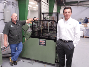 Mike Morgan (Production Manager) and Mallery Mele (Owner), stand next to                                    Mele Printing's new Kluge EHF.
